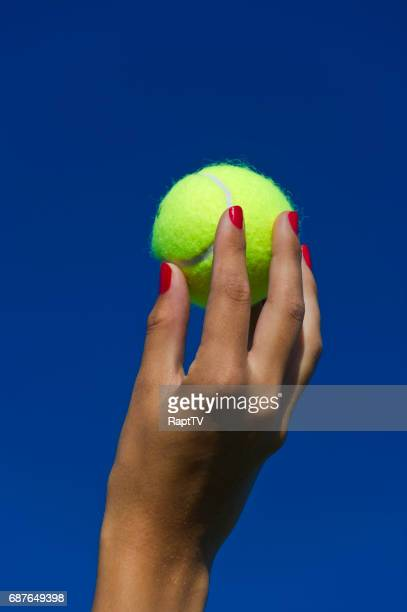 A tennis player holds up the tennis ball to serve.