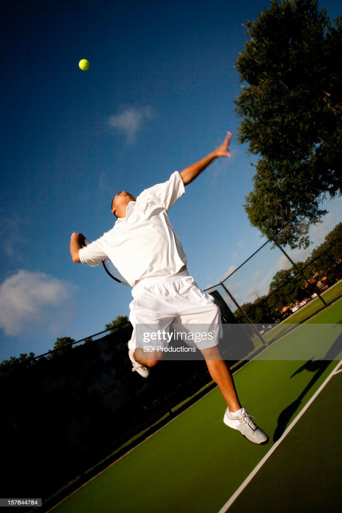 Tennis Player in Mid Serve on a Deep Blue Sky : Stock Photo