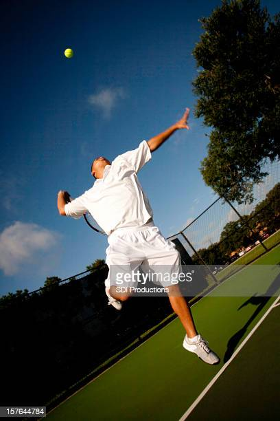 Tennis Player in Mid Serve on a Deep Blue Sky