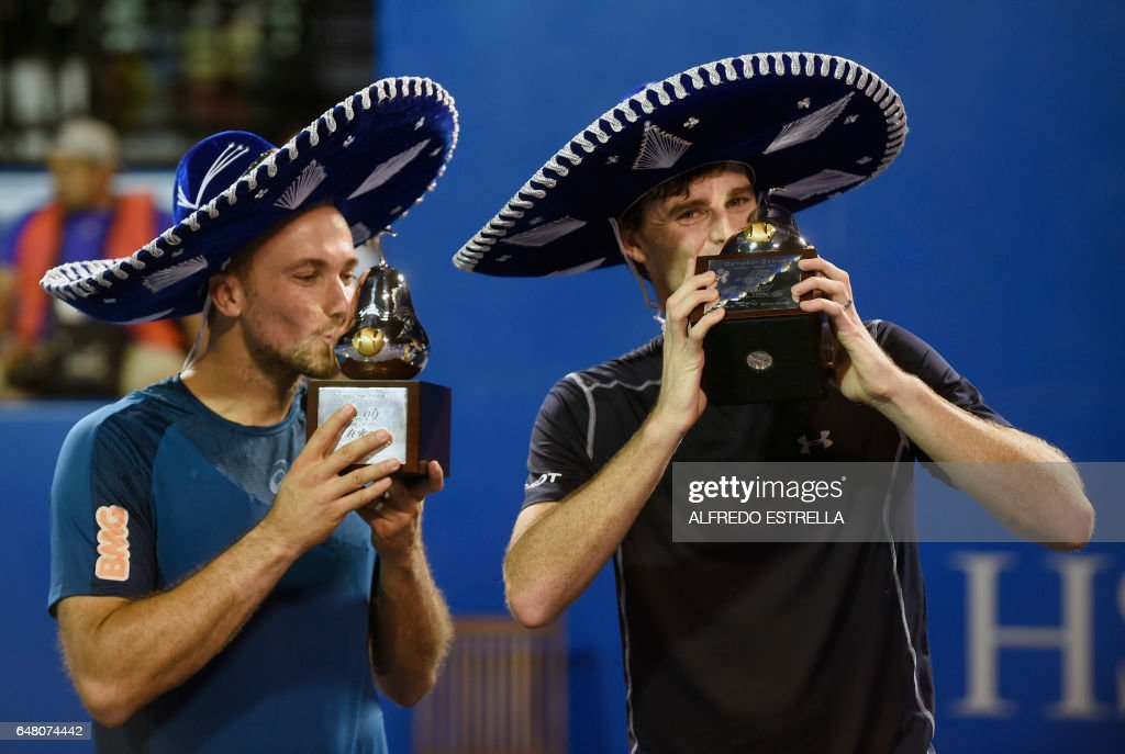 UK tennis player Jamie Murray (R) and Brazilian tennis player Bruno Soares kiss their trophies after winning the Mexican Tennis Open doubles final match against US tennis player Feliciano Lopez and Spanish tennis player John Isner in Acapulco, Guerrero State, Mexico, on March 4, 2017. /