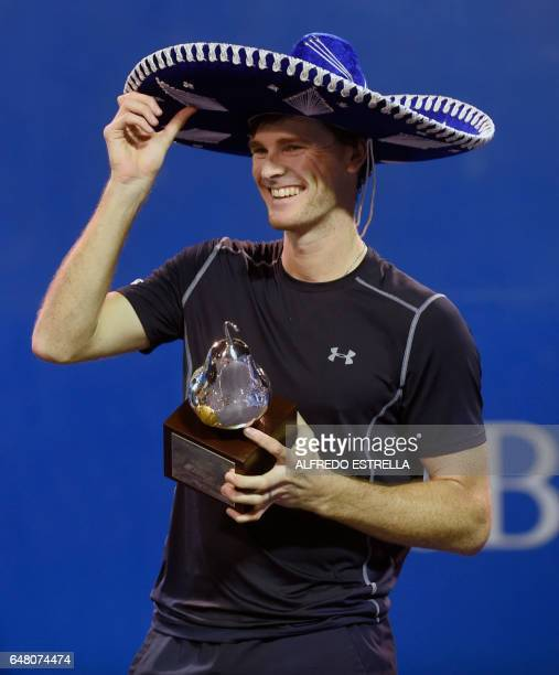 UK tennis player Jamie Murray poses with the trophy after winning with Brazilian tennis player Bruno Soares the Mexican Tennis Open doubles final...