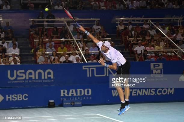 Tennis player John Isner serves to Australian tennis player Nick Kyrgios during their Mexico ATP 500 Open men's single tennis semifinal match in...