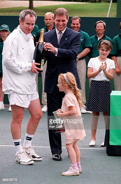 Tennis player John McEnroe smiling as daughter Anna carries cup her father won at charity tennis event at Buckingham Palace for the National Society...