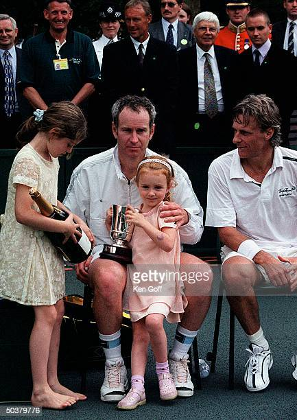 Tennis player John McEnroe w two of his daughters opponent Bjorn Borg at charity tennis event at Buckingham Palace for the National Society for the...