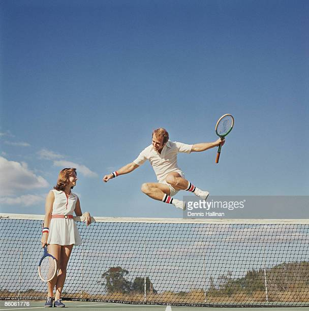 Tennis player jumping over net while woman smiles