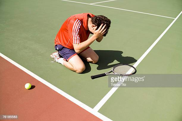 A tennis player kneeling on the court in defeat