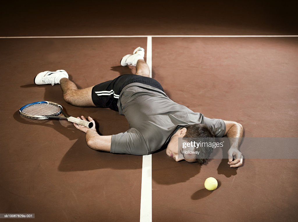 Tennis player lying unconscious on court : Stock Photo