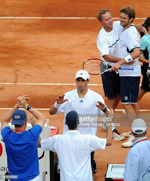 US tennis player Mardy Fish celebrates with teammates as Mike Bryan is congratulated by coach Patrick McEnroe after defeating Spanish Feliciano Lopez...