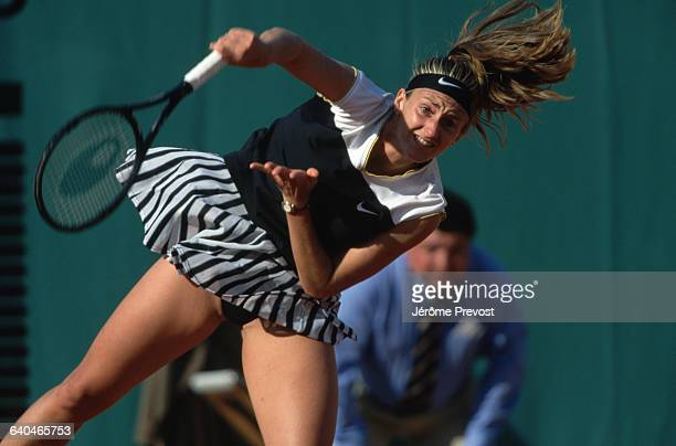 Tennis player Mary Pierce throws herself into a serve during a match at the 1997 French Open