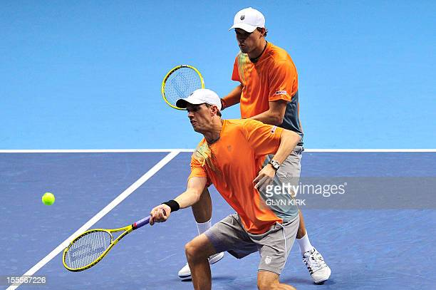 US tennis player Mike Bryan hits a return as his partner Bob Bryan watches against Spain's Marc Lopez and Spain's Marcel Granollers during their...