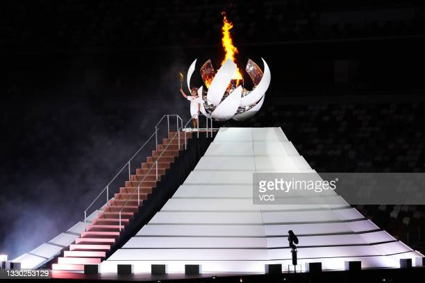 Tennis player Naomi Osaka lights the cauldron with the Olympic torch during the Opening Ceremony of the Tokyo 2020 Olympic Games at Olympic Stadium...