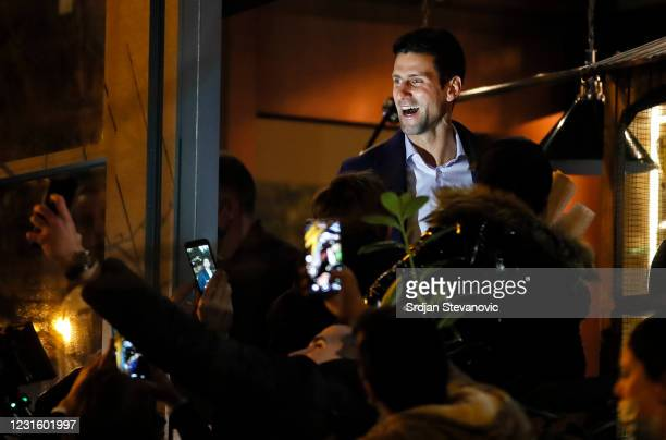 """Tennis player Novak Djokovic celebrates 311 weeks as world number one with his family and supporters in front of family restaurant """"Novak"""" on March..."""