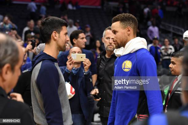 Tennis player Novak Djokovic talks with Stephen Curry of the Golden State Warriors before the game against the LA Clippers on October 30 2017 at...