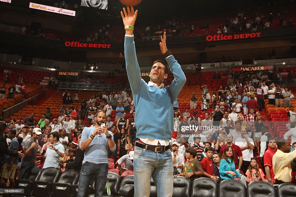 Tennis player Novak Djokovic tries a hand with basketball during a game between the Charlotte Bobcats and the Miami Heat on March 24, 2013 at American Airlines Arena in Miami, Florida.