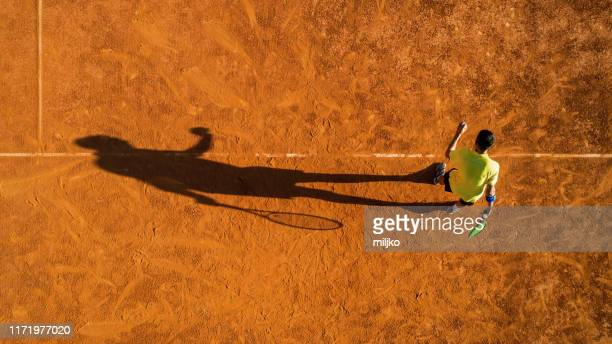 tennis player on service on clay court - tennis stock pictures, royalty-free photos & images