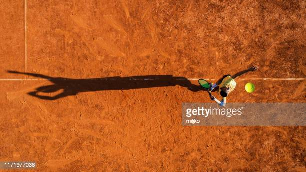 tennista in servizio su campo in terra battuta - tennis foto e immagini stock