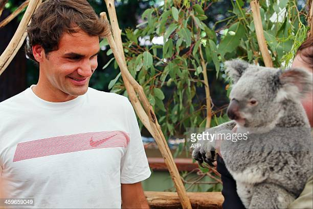 Tennis player Roger Federer of Switzerland relaxes with a koala during a visit to the Lone Pine Sanctuary in Brisbane on December 29 2013 The former...