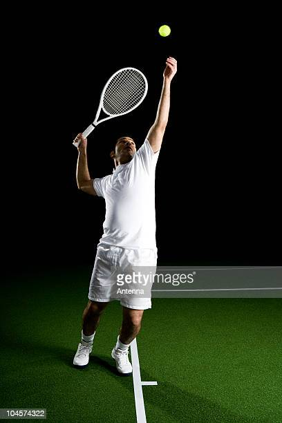 A tennis player serving a ball, portrait, studio shot