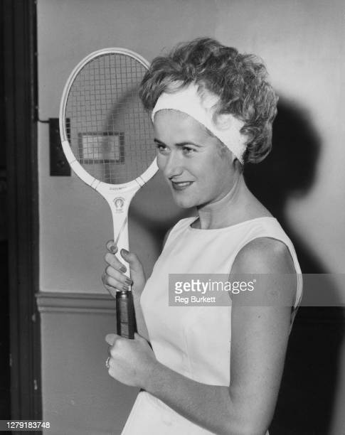 Tennis player Shirley Bloomer of Great Britain demonstrates the new Teddy Tinling design for French of London Sportsgirl Wig with a terry towling...