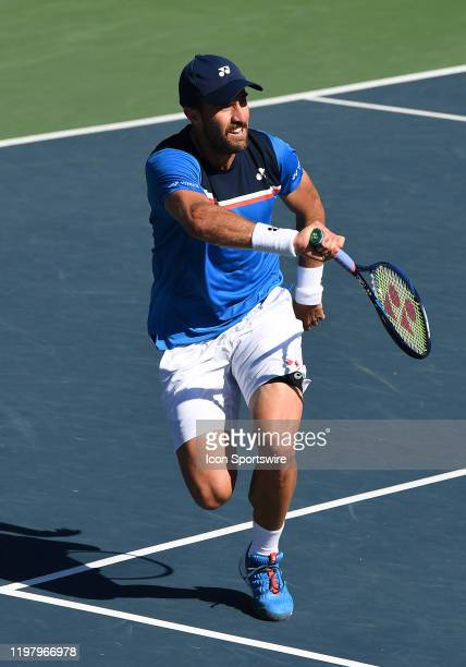 Tennis player Steve Johnson returns a shot in a semifinals match played during the Oracle Challenger Series tennis tournament played on February 1,...