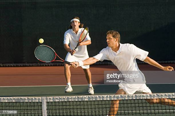 tennis player swinging at ball - doubles stock photos and pictures