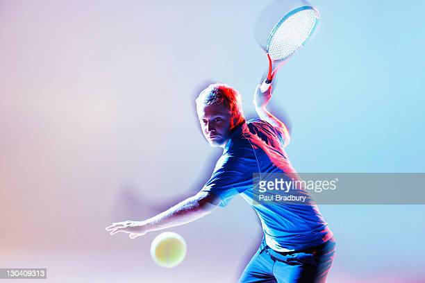 tennis player swinging racket - studio shot stockfoto's en -beelden