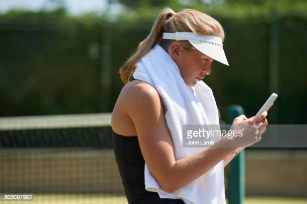 tennis player using smartphone - tennis player stock pictures, royalty-free photos & images