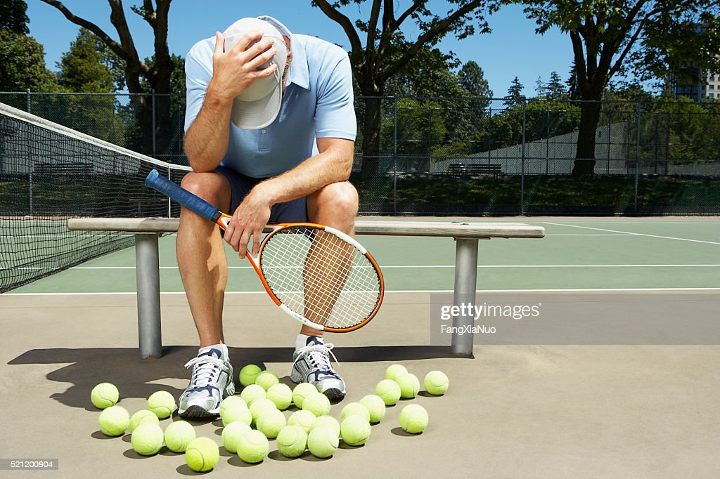 Tennis player with his head in his hands : Stock Photo