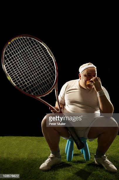 Tennis player with large racquet sitting