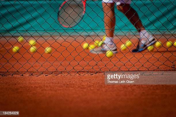 Tennis player with tennis balls seen through fence