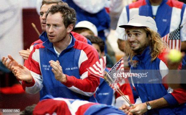 US tennis players John McEnroe and Andre Agassi cheer for teammate Jim Courier as he plays Switzerland's Marc Rosset in the second match of the Davis...