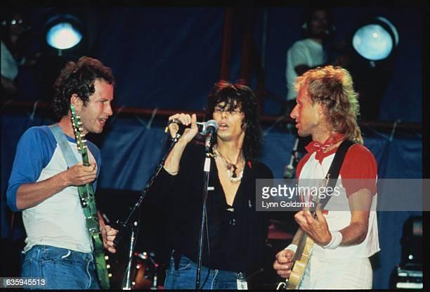Tennis players John McEnroe and Vitas Gerulaitis play electric guitars as Steven Tyler of Aerosmith sings.