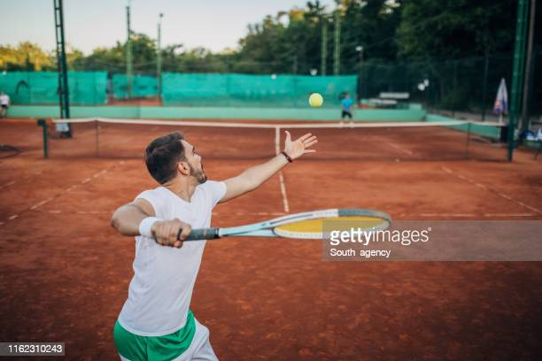 tennis players playing a match outdoors - tennis player stock pictures, royalty-free photos & images