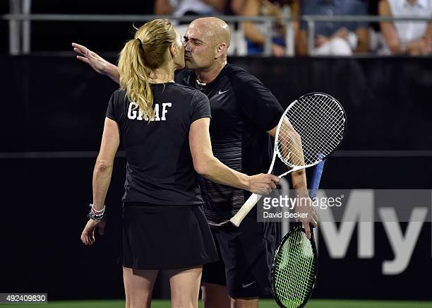 Tennis players Stefanie Graf and her husband Andre Agassi react after scoring a point during play at the Mylan World TeamTennis Smash Hits charity...