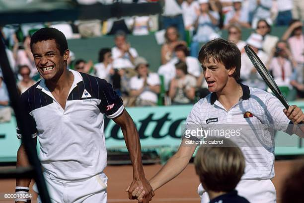 Tennis players Yannick Noah and Henri Leconte compete in a Men's Doubles match.