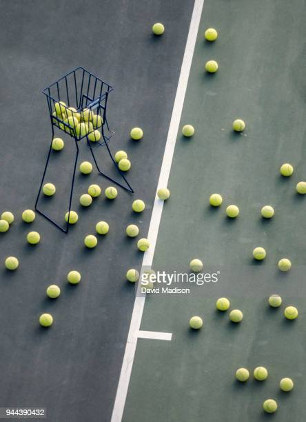 tennis practice balls and basket on court - tennis ball stock pictures, royalty-free photos & images