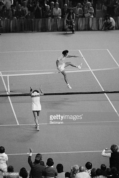 Tennis pro Billie Jean King claps her hands as Bobby Riggs jumps the net to congratulate his opponent in the $100,000 winner-take-all tennis match....