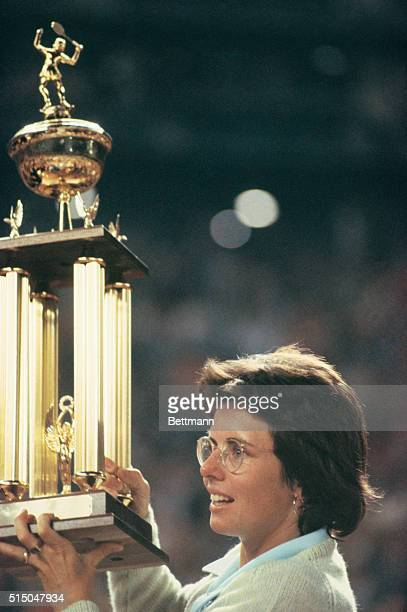 Tennis pro Billie Jean King holds her newly won trophy high after beating Bobby Riggs in their $100000 winner take all 'Battle of the Sexes' tennis...