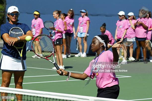 Tennis pro Gigi Fernandez watches approvingly as a youngster hits a return during a Leadership Day for Girls clinic at the US Open at Flushing...