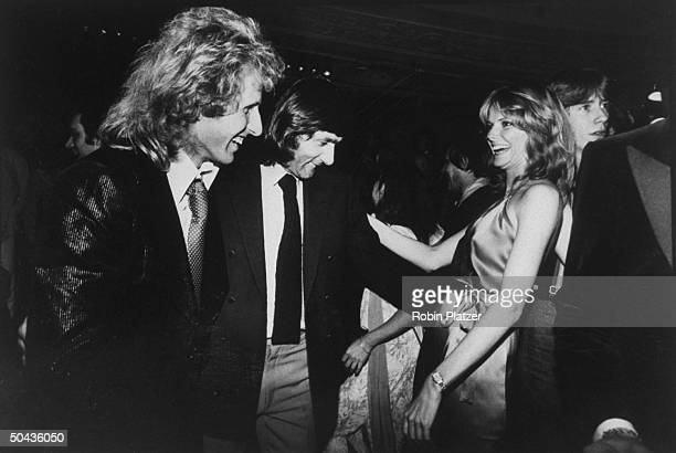 Tennis pros Vitas Gerulaitis and Ilie Nastase admiring the outfit of model Cheryl Tiegs on the dance floor of Studio 54
