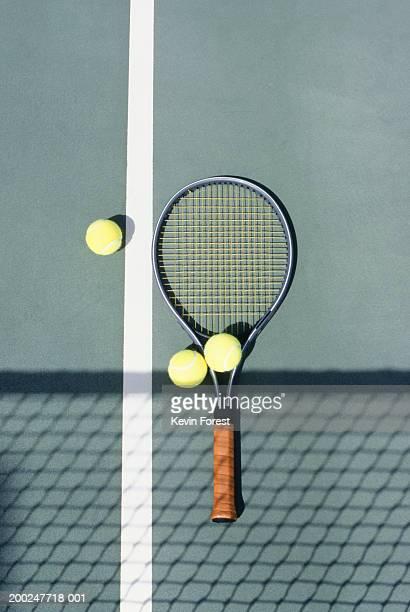 Tennis racket and balls lying on court