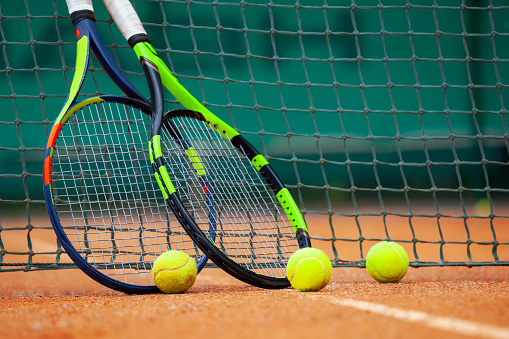 Tennis rackets and balls leaned against the net. 1171084311