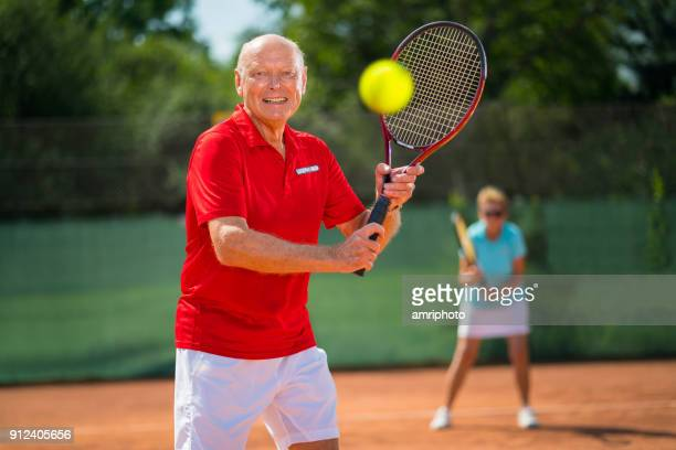 tennis -  smiling 73 years old senior tennis player ball backhand stroke - tennis player stock pictures, royalty-free photos & images