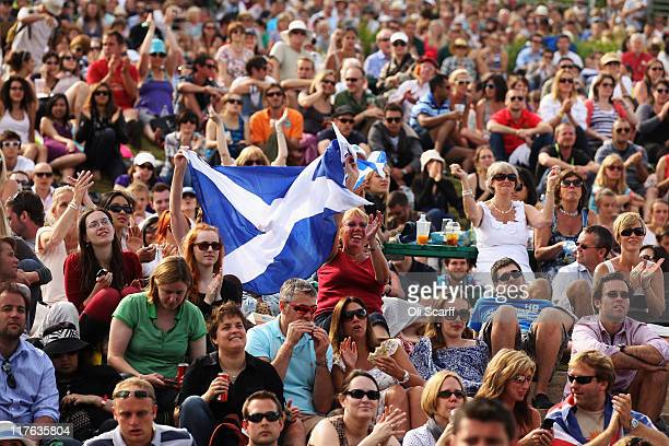 Tennis spectators wave a Scotland flag while watching Andy Murray's quarter final match against Feliciano Lopez of Spain on Day Nine of the Wimbledon...