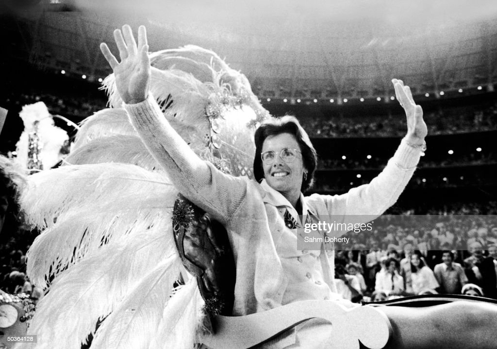 Tennis star Billie Jean King waving to fans from float as she is carried into stadium prior to her tennis match with Bobby Riggs.