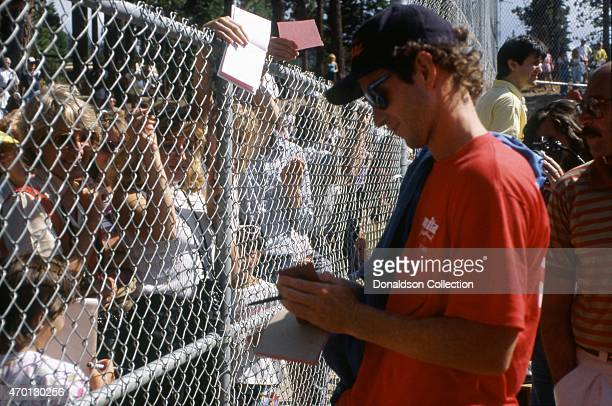 Tennis star John McEnroe signs autographs at an exhibition softball game for Cerebral Palsy Research at the Mita Sports Festival on July 25 1986 in...