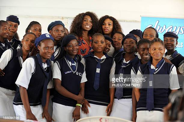 US tennis superstars Venus and Serena Williams pose for a photograph with students of the Federal Government College in the Ikoyi district of Lagos...