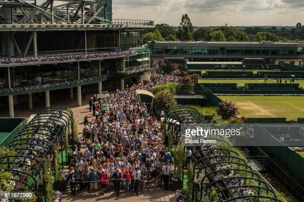 Tennis supporters make their way to courts ahead day seven of the Wimbledon Lawn Tennis Championships at the All England Lawn Tennis and Croquet Club...