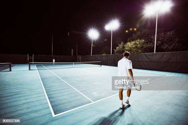 Tennis teammates practicing together on outdoor court at night