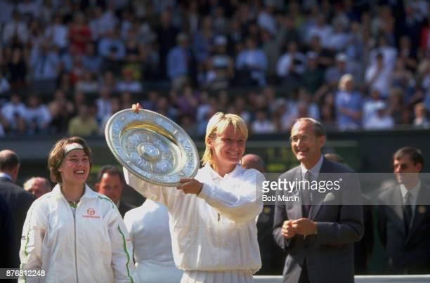 Wimbledon Czech Republic Jana Novotna hoisting Rosewater Dish after grabbing it in jest from Switzerland Martina Hingis after Women's Final match at...